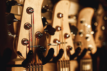 Uppermost Part Of The Guitar. Close View Of Several Acoustic Guitar Headstocks With Tuning Keys For Adjusting Guitar Strings. Music Shop.