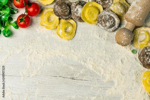 Keuken foto achterwand Assortiment Homemade fresh Italian ravioli pasta on white wood table with flour, basil, tomatoes,background,top view.