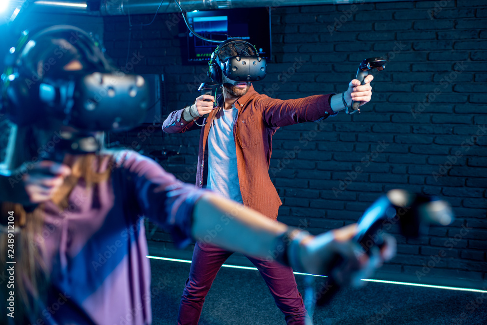Fototapeta Man and woman playing game using virtual reality headset and gamepads in the dark room of the playing club