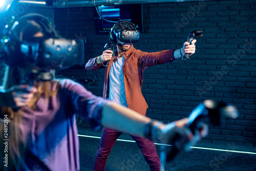 Fotografie, Tablou  Man and woman playing game using virtual reality headset and gamepads in the dar