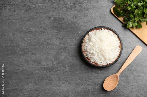 Boiled rice in bowl served on grey table, top view with space for text Fototapeta