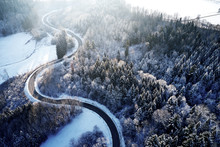 Aerial Drone View Of A Curved Winding Road Through The Forest Up In The Mountains In The Winter With Snow Covered Trees And Curved Streets In Winter While Sunset And Sun Rays Casting Trough