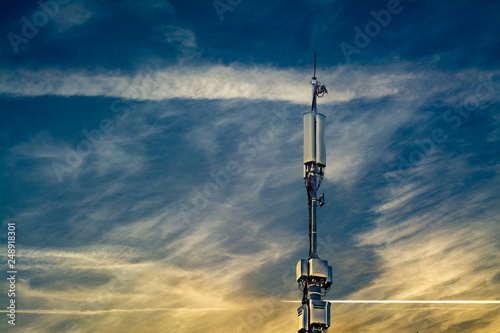 Valokuva  A pillar with repeaters of cellular communication cells against a sunset cloudy