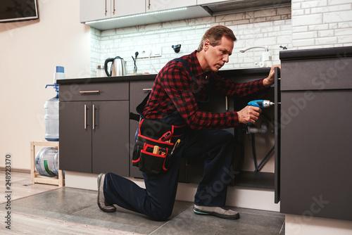 Handyman at work. Repairing kitchen shelves by perforator Fototapet