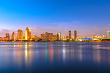 Panoramic Landscape Of San Diego Skyline With Illuminated Skyscrapers Reflecting In San Diego Bay At Twilight. Districts Of Waterfront Marina Skyline And Urban Downtown Cityscape At Sunset Light.