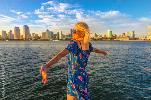 Obraz na plátne Happy tourist woman looking at San Diego Downtown skyline with skyscrapers in California, USA from Coronado Island