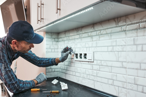 Obraz All is safe. Side view of young handyman setting new sockets - fototapety do salonu