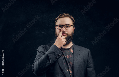 Fotografie, Obraz  Portrait of a bearded guy in a formal jacket with a silly look picks a finger in his nose
