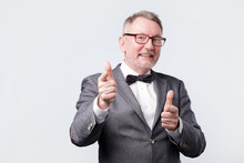 Business Senior Man Pointing At You Wearing Suit And Bow Tie