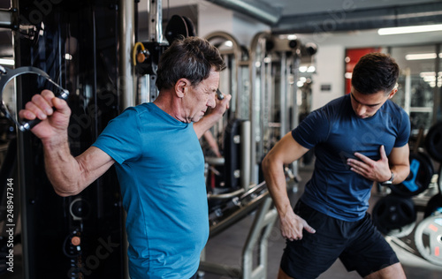 A senior man with a young trainer doing strength workout exercise in gym.