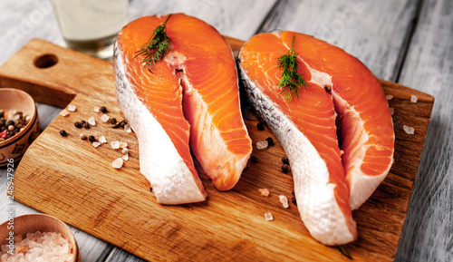 Fotografie, Obraz  Raw salmon steaks with spices, herbs, salt and lemon on a wooden table backgroun