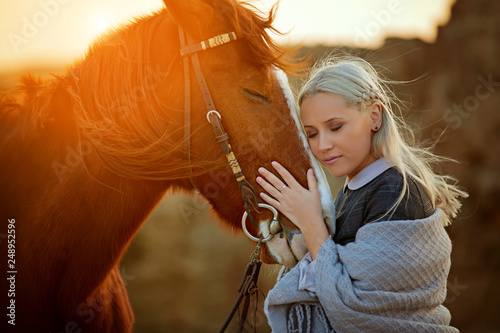 Fotografía  Beautiful female in stylish outfit keeping eyes closed and hugging head of amazi