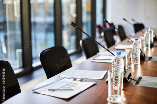 Fotografía  Business documents, plastic bottles of water, glasses and microphones along tabl