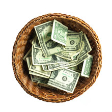Brown Wicker Donation Basket Filled With US One And Five Doallar Bills Isolated On A White Background