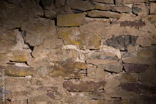 Fotografering  Cracked dilapidated masonry wall lit diagonally