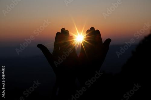 Carta da parati Faith of christian concept: Spiritual prayer hands over sun shine with blurred b