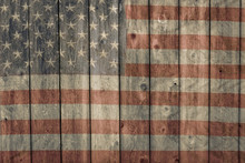 Faded American Flag Painted On The Side Of An Old Weathered Wooden Barn