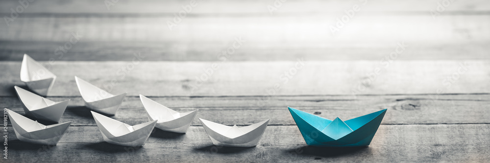 Fototapeta Blue Paper Boat Leading A Fleet Of Small White Boats On Wooden Table With Vintage Effect - Leadership Concept