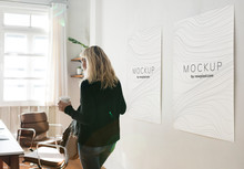 Woman In A Working Space With Poster Design Mockups