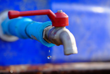 Drops Of Water Under The Blue Water Pipes And Red Faucets.