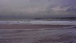 Ocean day time; Few men are swimming; Purple light fills air; grey and blue clouds in a sky are formed and feel stationary. It is a bright and partially sunny day. Cornwall, UK. Filmed in HD
