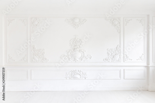 Fototapeta Beautiful ornate white decorative plaster mouldings in studio. The white wall is decorated with exquisite elements of plaster stucco obraz