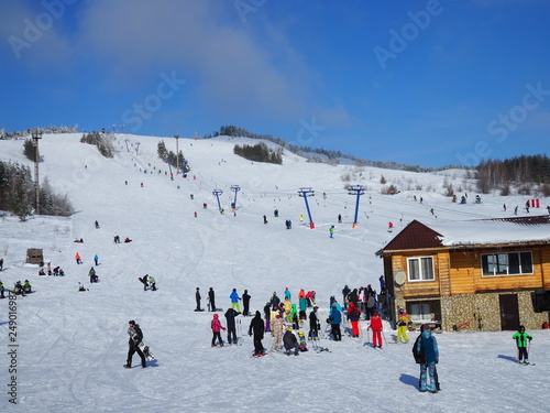 Fotografía  The slope of the ski resort with a ski lift and athletes with skis and snowboards frosty day