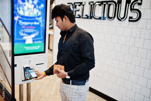 Indian man customer at store place orders and pay by contactless credit card on mobile phone through self pay floor kiosk for fast food, payment terminal Canvas Print
