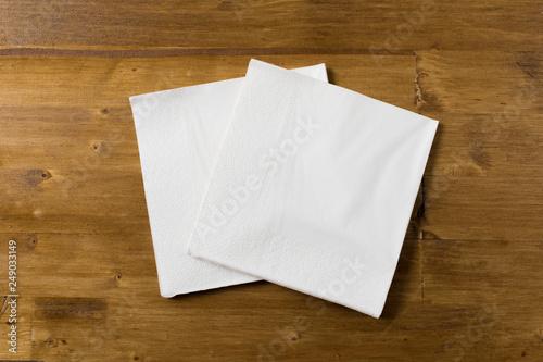 Fototapeta white paper napkin on wooden background. obraz