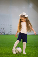 A Little Girl Kicking The Ball On The Football Field Playing The Game