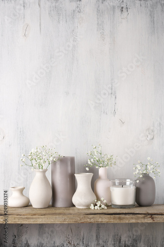 Stampa su Tela White flowers in neutral colored vases and candles