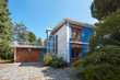 Villa with garden and garage in a sunny summer day, clear blue sky