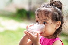 Cute Child Girl Drinking Clear...
