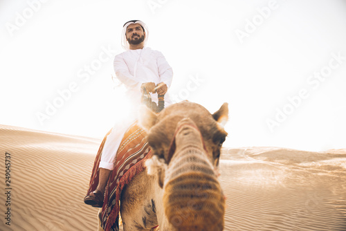 Poster Abou Dabi Man wearing traditional clothes, taking a camel out on the desert sand, in Dubai