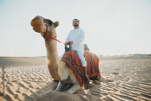 Man wearing traditional clothes, taking a camel out on the desert