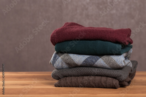 Fotografía  Bunch of knitted warm sweaters with different knitting patterns folded in stack