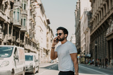 Young Urban Professional Man Using Smart Phone. Hipster Coworker Holding Mobile Smartphone Using App Texting Sms Message Wearing Sunglasses.