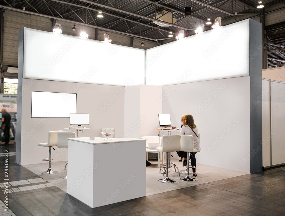 Fototapeta Blank mock up creative exhibition stand design with shapes. Booth template, Empty exhibition kiosk, with copy space, futuristic interior suspending lighting fixtures, computer and tv screen.