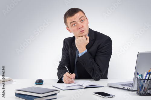 Fotografija  Serious businessman skeptically looking at you sitting at his desk on gray background
