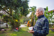 Portrait of elderly man holding a cup of coffee in his garden.