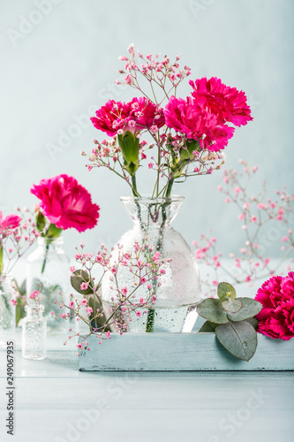 Photo  Bouquet of pink carnation in glass vase on light turquoise wooden background