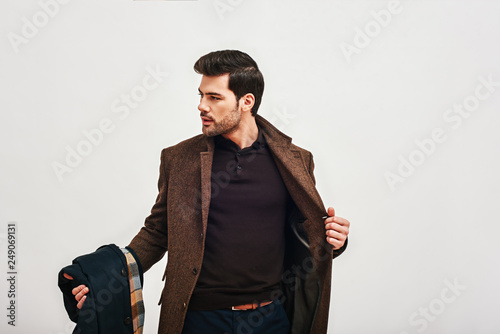 Obraz Always perfect. Stylish dark-haired man standing, holding his coat and looking away isolated over white background - fototapety do salonu