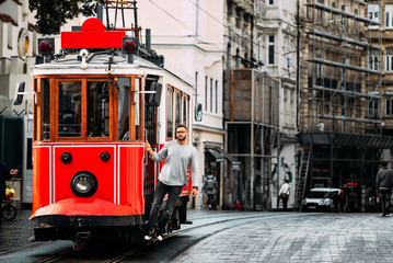 Man in a vintage tram on the Taksim Istiklal street in Istanbul. Man on public transport. Old Turkish tram on Istiklal street, Turkey. Portrait of a smiling young man posing on a city street.