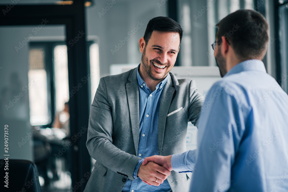 Fototapeta Portrait of cheerful young manager handshake with new employee.