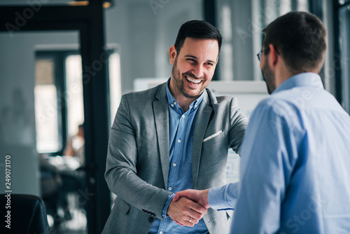 Slika na platnu Portrait of cheerful young manager handshake with new employee.