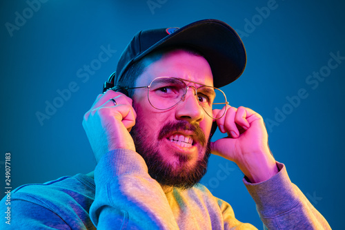 Enjoying his favorite music. Scared young stylish man in sunglasses with headphones listening sound while standing against blue neon background - 249077183