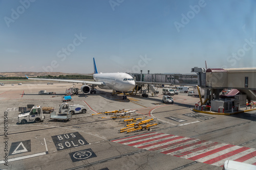 Poster Aeroport View of the runway of an airport with a plane parked, luggage transport vans and other vehicles