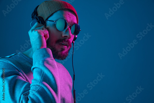 Fond de hotte en verre imprimé Magasin de musique Enjoying his favorite music. Happy young stylish man in hat and sunglasses with headphones listening and smiling while standing against blue neon background
