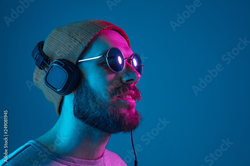 Poster Magasin de musique Enjoying his favorite music. Happy young stylish man in hat and sunglasses with headphones listening and smiling while standing against blue neon background