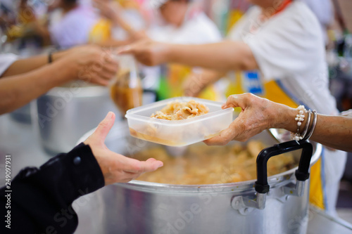 Valokuva  The hand of a beggar received food from a compassionate person : giving food to the poor